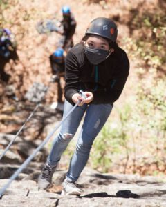 student rock climbing wearing helmet and face mask