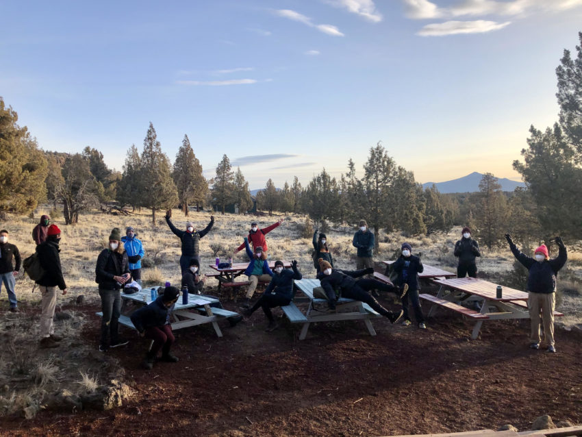 A group of Northwest Outward Bound Students wearing masks and social distancing around a picnic table with mountains in the distance