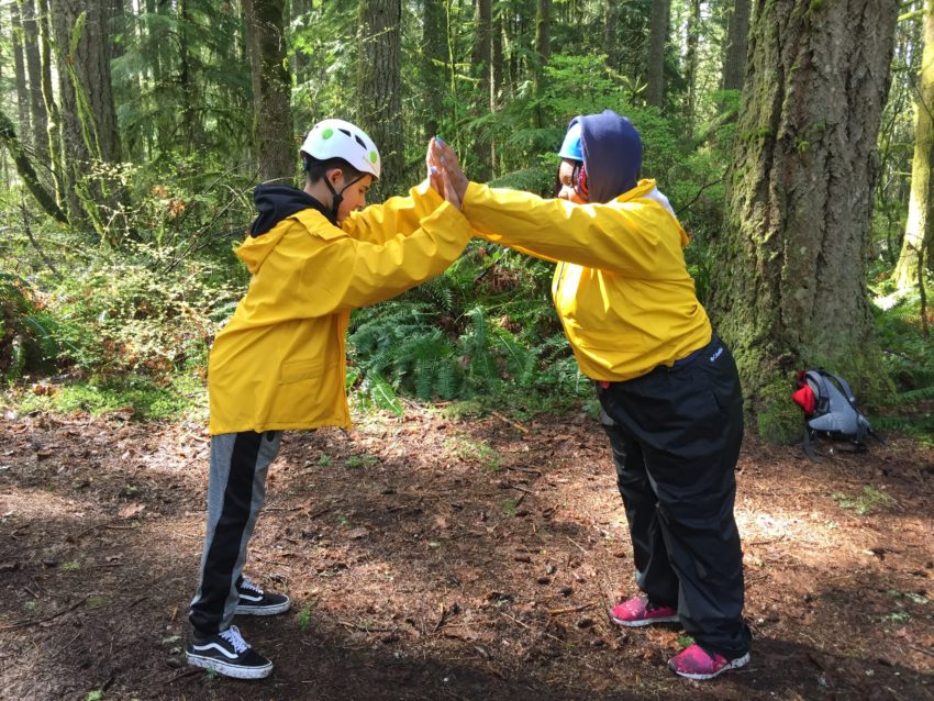 two outward bound students wearing yellow rain jackets assist each other during a challenge course